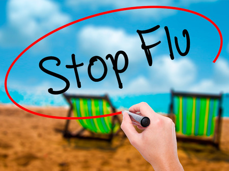 Man Hand writing Stop Flu with black marker on visual screen. Isolated on sunbed on the beach. Business,  technology, internet concept. Stock Photo Stock Photo