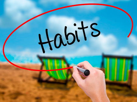 Man Hand writing Habits  with black marker on visual screen. Isolated on sunbed on the beach. Business, technology, internet concept. Stock Photo Stock Photo