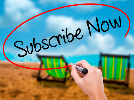 Man Hand writing Subscribe Now with black marker on visual screen. Isolated on sunbed on the beach. Business, technology, internet concept. Stock Photo