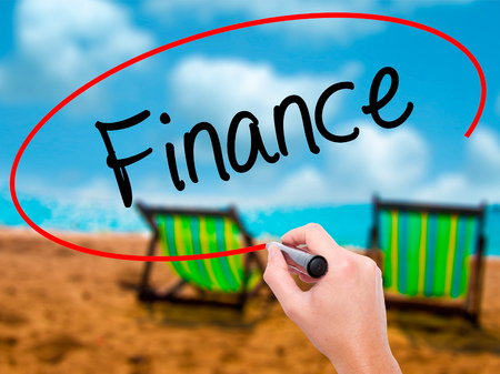 Man Hand writing Finance with black marker on visual screen. Isolated on sunbed on the beach. Business, technology, internet concept. Stock Photo