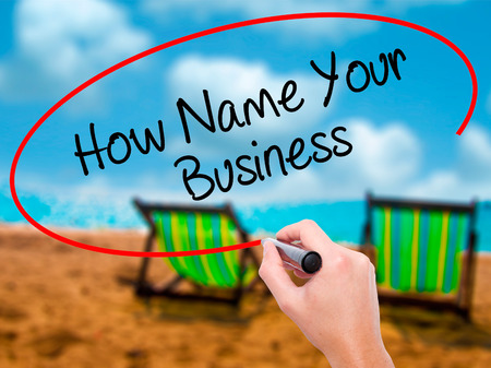 Man Hand writing How Name Your Business with black marker on visual screen. Isolated on sunbed on the beach. Business, technology, internet concept. Stock Photo