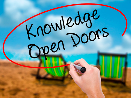 Man Hand writing  Knowledge Open Doors  with black marker on visual screen. Isolated on sunbed on the beach. Business, technology, internet concept. Stock Photo