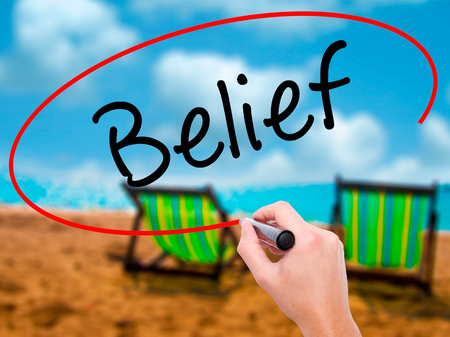 posit: Man Hand writing Belief with black marker on visual screen. Isolated on sunbed on the beach. Business, technology, internet concept. Stock Photo