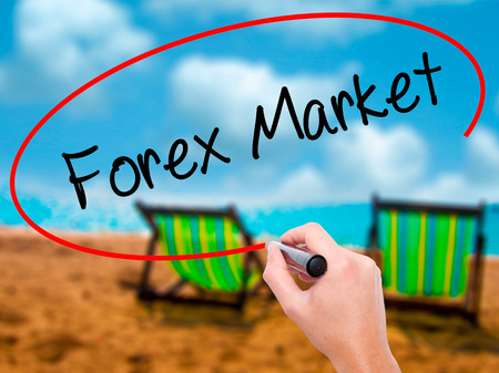 Man Hand writing  Forex Market with black marker on visual screen. Isolated on sunbed on the beach. Business, technology, internet concept. Stock Photo Stock Photo