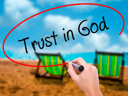 Man Hand writing Trust in God with black marker on visual screen. Isolated on sunbed on the beach. Business, technology, internet concept. Stock Photo