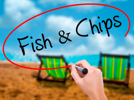 Man Hand writing Fish & Chips with black marker on visual screen. Isolated on sunbed on the beach. Business, technology, internet concept. Stock Photo Stock Photo