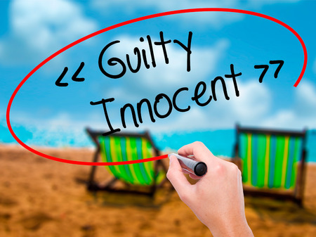 fair trial: Man Hand writing Guilty - Innocent with black marker on visual screen. Isolated on sunbed on the beach. Business, technology, internet concept. Stock Photo