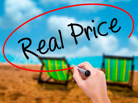 Man Hand writing Real Price with black marker on visual screen. Isolated on sunbed on the beach. Business, technology, internet concept. Stock Photo Stock Photo