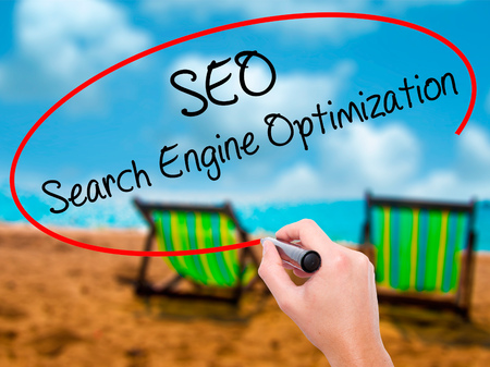 Man Hand writing SEO Search Engine Optimization with black marker on visual screen. Isolated on sunbed on the beach. Business, technology, internet concept. Stock Photo Stock Photo