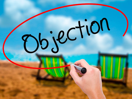 Man Hand writing Objection with black marker on visual screen. Isolated on sunbed on the beach. Business, technology, internet concept. Stock Photo