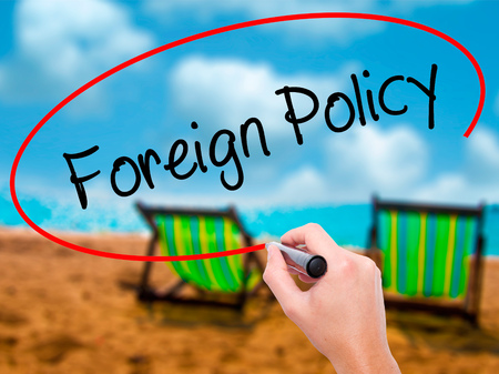 Man Hand writing Foreign Policy with black marker on visual screen. Isolated on sunbed on the beach. Business, technology, internet concept. Stock Photo