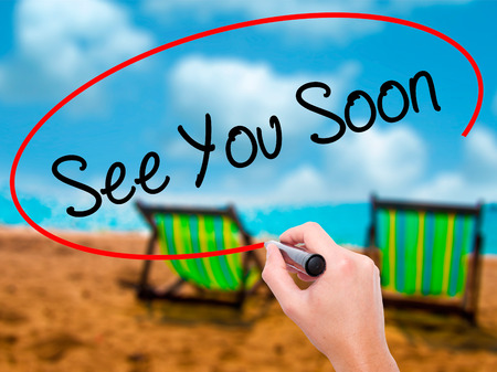 Man Hand writing See You Soon with black marker on visual screen. Isolated on sunbed on the beach. Business, technology, internet concept. Stock Photo