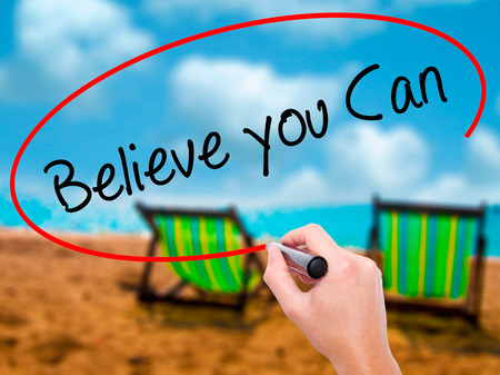 Man Hand writing Believe you Can with black marker on visual screen. Isolated on sunbed on the beach. Business, technology, internet concept. Stock Photo
