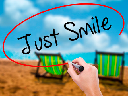 working hours: Man Hand writing Just Smile with black marker on visual screen. Isolated on sunbed on the beach. Business, technology, internet concept. Stock Photo Stock Photo