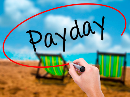 Man Hand writing Payday with black marker on visual screen. Isolated on sunbed on the beach. Business, technology, internet concept. Stock Photo