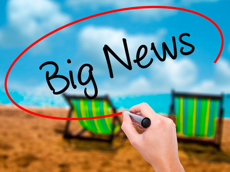 annoucement: Man Hand writing Big News with black marker on visual screen. Isolated on sunbed on the beach. Business, technology, internet concept.