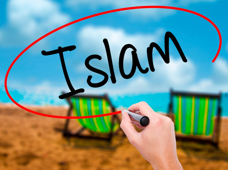 Man Hand writing Islam with black marker on visual screen. Isolated on sunbed on the beach. Business, technology, internet concept. Stock Photo
