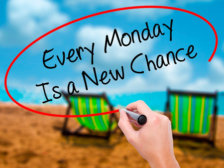 another way: Man Hand writing Every Monday Is a New Chance with black marker on visual screen. Isolated on sunbed on the beach. Business, technology, internet concept. Stock Photo
