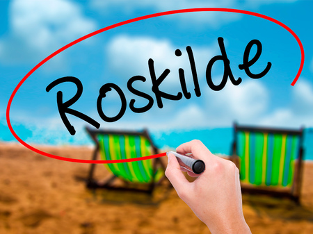humanismo: Man Hand writing Roskilde  with black marker on visual screen. Isolated on sunbed on the beach. Business, technology, internet concept. Stock Photo