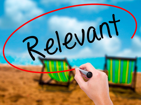 objectivism: Man Hand writing Relevant with black marker on visual screen. Isolated on sunbed on the beach. Business, technology, internet concept. Stock Photo