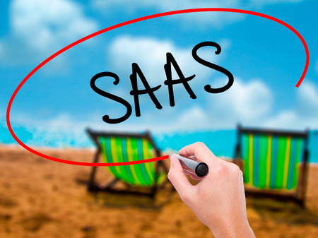 Man Hand writing SAAS with black marker on visual screen. Isolated on sunbed on the beach. Business, technology, internet concept. Stock Photo
