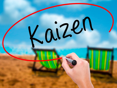 Man Hand writing Kaizen with black marker on visual screen. Isolated on sunbed on the beach. Business, technology, internet concept. Stock Photo