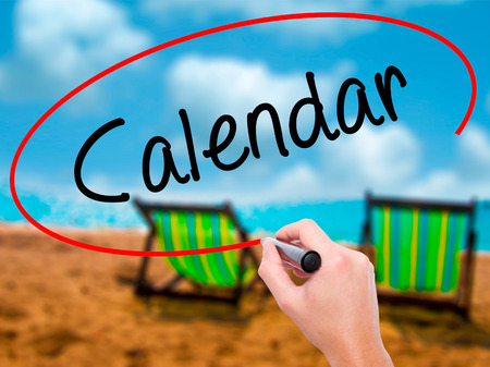 Man Hand writing Calendar   with black marker on visual screen. Isolated on sunbed on the beach. Business, technology, internet concept.