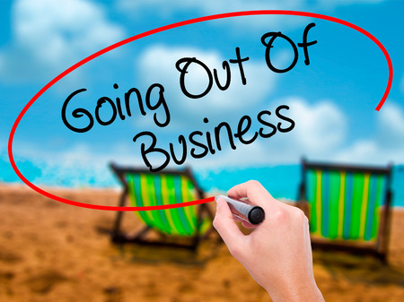 retailer: Man Hand writing Going Out Of Business with black marker on visual screen. Isolated on sunbed on the beach. Business, technology, internet concept. Stock Photo