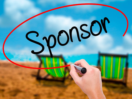 Man Hand writing Sponsor with black marker on visual screen. Isolated on sunbed on the beach. Business, technology, internet concept. Stock Photo Stock Photo