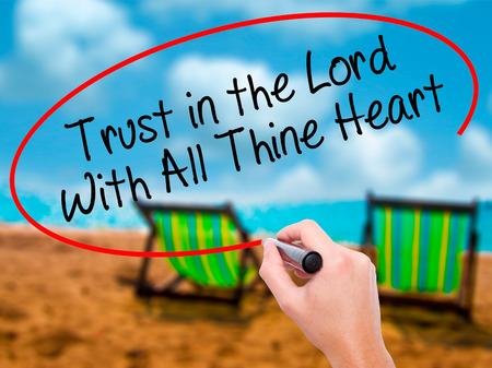 Man Hand writing Trust in the Lord With All Thine Heart with black marker on visual screen. Isolated on sunbed on the beach. Business, technology, internet concept. Stock Photo