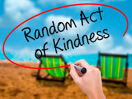 helping others: Man Hand writing Random Act of Kindness with black marker on visual screen. Isolated on sunbed on the beach. Business, technology, internet concept. Stock Photo Stock Photo