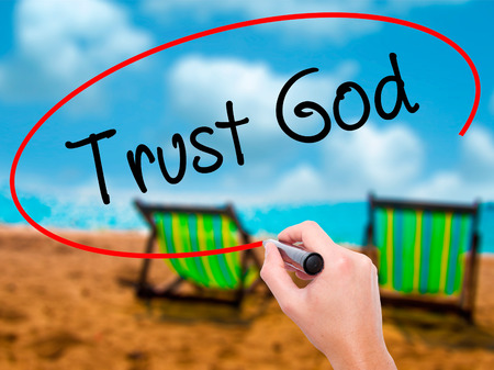 trust in god: Man Hand writing Trust God  with black marker on visual screen. Isolated on sunbed on the beach. Business, technology, internet concept. Stock Photo