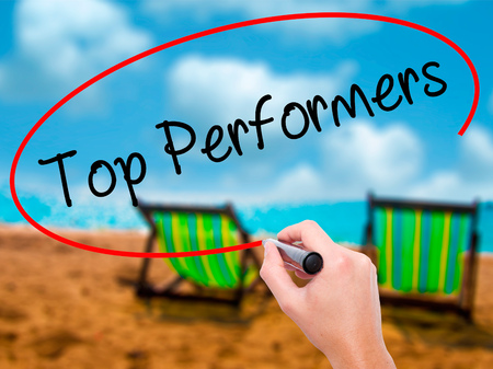 Man Hand writing Top Performers with black marker on visual screen. Isolated on sunbed on the beach. Business, technology, internet concept. Stock Photo
