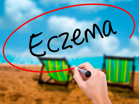 Man Hand writing Eczema with black marker on visual screen. Isolated on sunbed on the beach. Business, technology, internet concept. Stock Photo