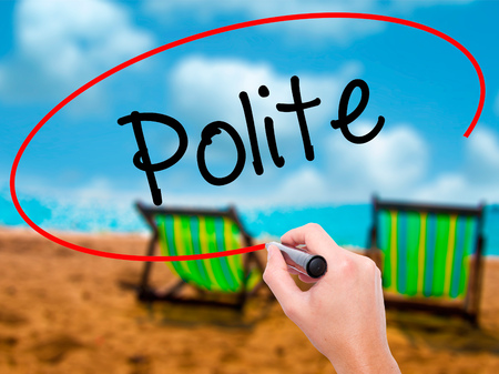 considerate: Man Hand writing Polite with black marker on visual screen. Isolated on sunbed on the beach. Business, technology, internet concept. Stock Photo Stock Photo