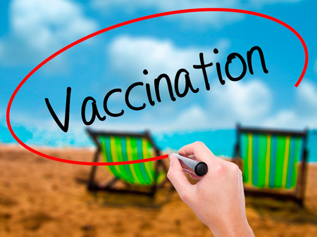 inoculate: Man Hand writing Vaccination  with black marker on visual screen. Isolated on sunbed on the beach. Business, technology, internet concept. Stock Photo
