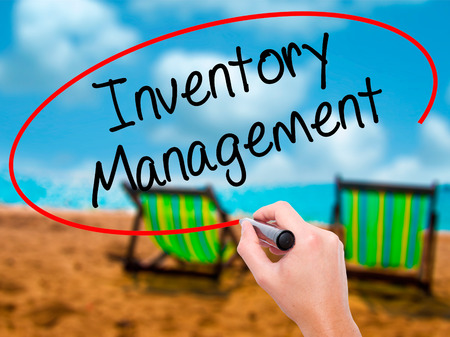 Man Hand writing Inventory Management with black marker on visual screen. Isolated on sunbed on the beach. Business, technology, internet concept. Stock Photo Stock Photo