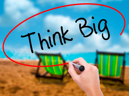 striving: Man Hand writing Think Big with black marker on visual screen. Isolated on sunbed on the beach. Business, technology, internet concept. Stock Photo