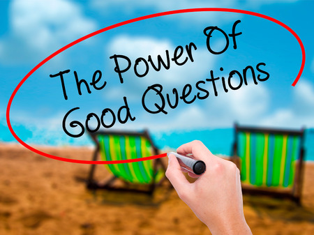 Man Hand writing The Power Of Good Questions with black marker on visual screen. Isolated on sunbed on the beach. Business, technology, internet concept. Stock Photo Stock Photo