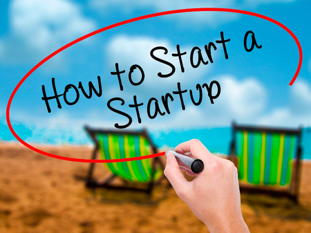 Man Hand writing How to Start a Startup with black marker on visual screen. Isolated on sunbed on the beach. Business, technology, internet concept. Stock Photo Stock Photo