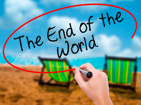 end of the world: Man Hand writing The End of the World with black marker on visual screen. Isolated on sunbed on the beach. Business, technology, internet concept. Stock Photo