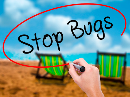 Man Hand writing Stop Bugs with black marker on visual screen. Isolated on sunbed on the beach. Business, technology, internet concept. Stock Photo