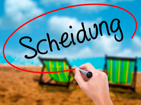 Man Hand writing Scheidung (Divorce in German) with black marker on visual screen. Isolated on sunbed on the beach. Business, technology, internet concept. Stock Photo Stock Photo