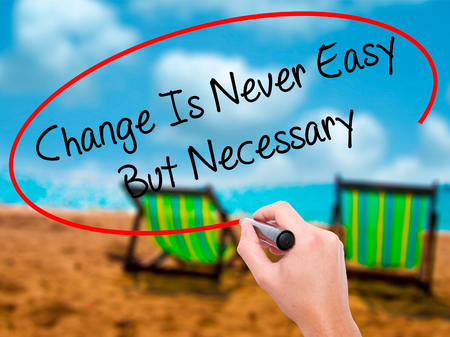 Man Hand writing Change Is Never Easy But Necessary with black marker on visual screen. Isolated on sunbed on the beach. Business, technology, internet concept. Stock Photo