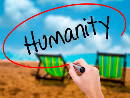 humanity: Man Hand writing Humanity  with black marker on visual screen. Isolated on sunbed on the beach. Business, technology, internet concept. Stock Photo Stock Photo
