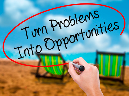Man Hand writing Turn Problems into Opportunities with black marker on visual screen. Isolated on sunbed on the beach. Business, technology, internet concept. Stock Photo Stock Photo