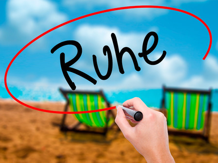 Man Hand writing Ruhe (Quiet in German) with black marker on visual screen. Isolated on sunbed on the beach. Business, technology, internet concept. Stock Photo