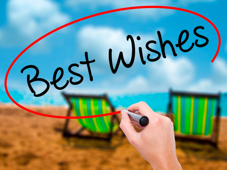Man Hand writing Best Wishes  with black marker on visual screen. Isolated on sunbed on the beach. Business, technology, internet concept. Stock Photo Banque d'images