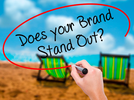 comunicación escrita: Man Hand writing Does your Brand Stand Out? with black marker on visual screen. Isolated on sunbed on the beach. Business, technology, internet concept. Stock Photo