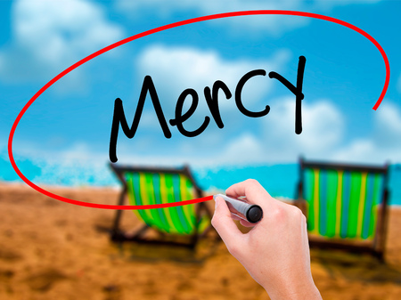 Man Hand writing Mercy with black marker on visual screen. Isolated on sunbed on the beach. Business, technology, internet concept. Stock Photo Stock Photo